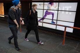 Nike Just Do It advertising behind walking couple