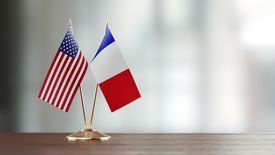 American And French Flag Pair On A Desk Over Defocused Background