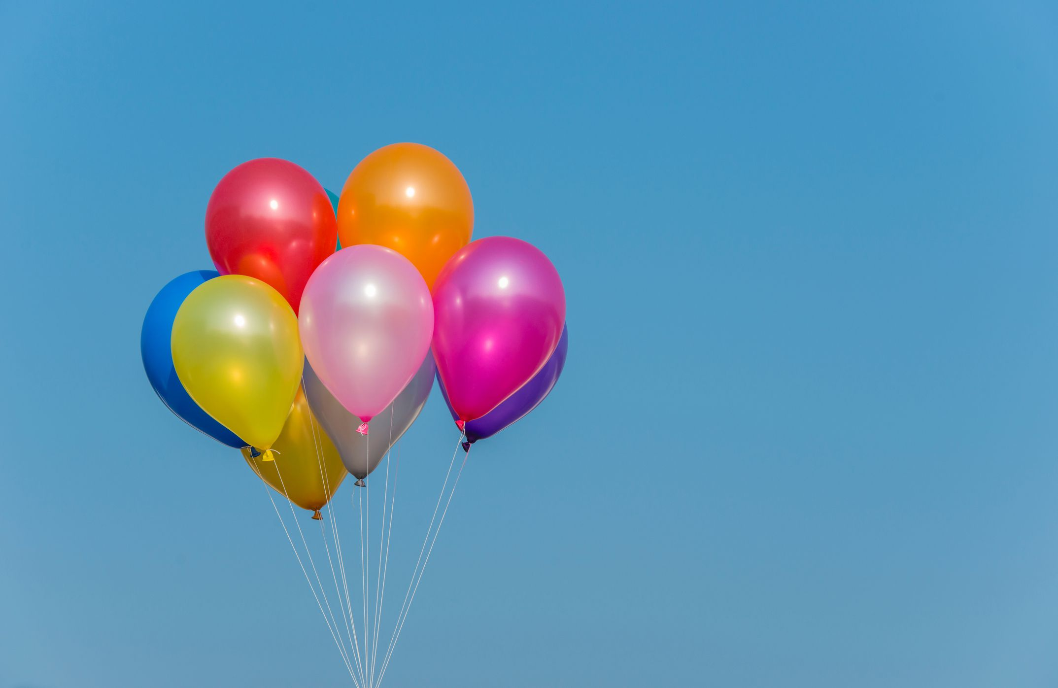 colorful helium balloons against the sky