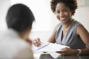 Black businesswoman showing report to client
