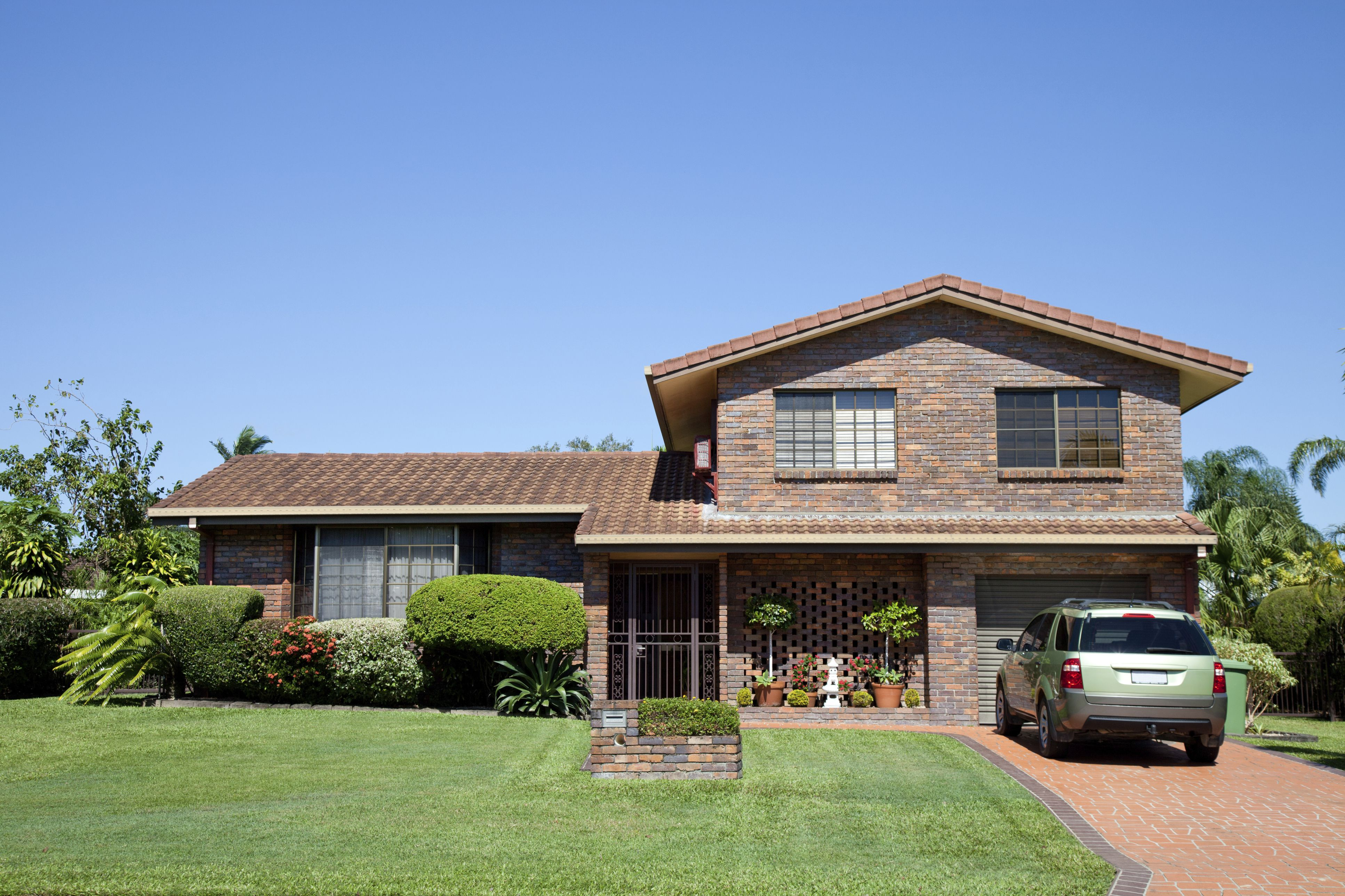 Front view of a tidy split level brown brick family home with green grass and blue sky and car in driveway.