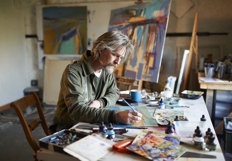 Artist working on painting concentrating in studio.