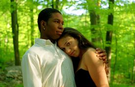 An interracial couple embraces in a forest