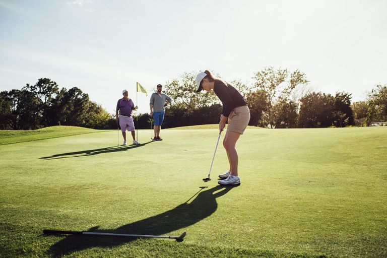Woman Putting On Golf Course With Family Watching