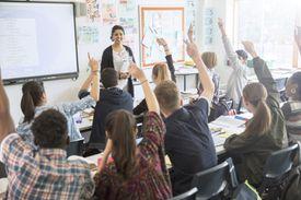 Teenage Students Raising Hands in Classroom