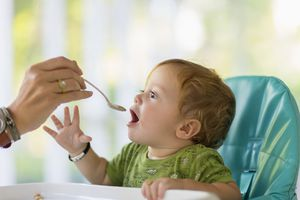 Caucasian mother feeding baby in high chair