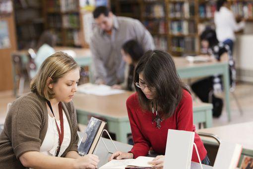 Bibliotecaria ayudando a joven.