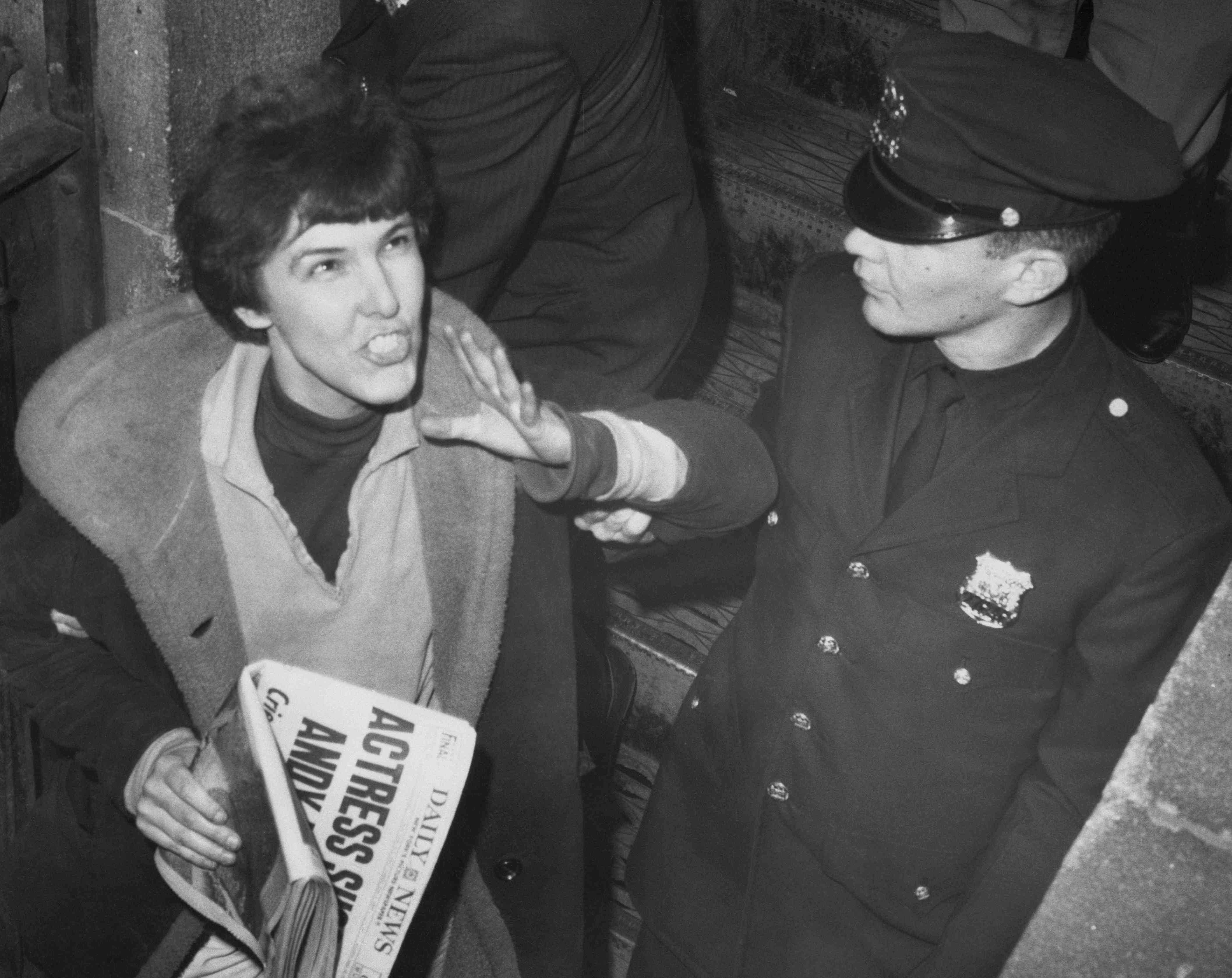 Black-and-white photo of Solanas shouting at a crowd as she's arrested