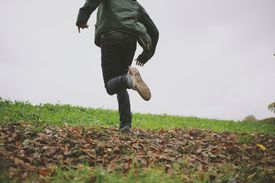Cropped shot of young man running in field