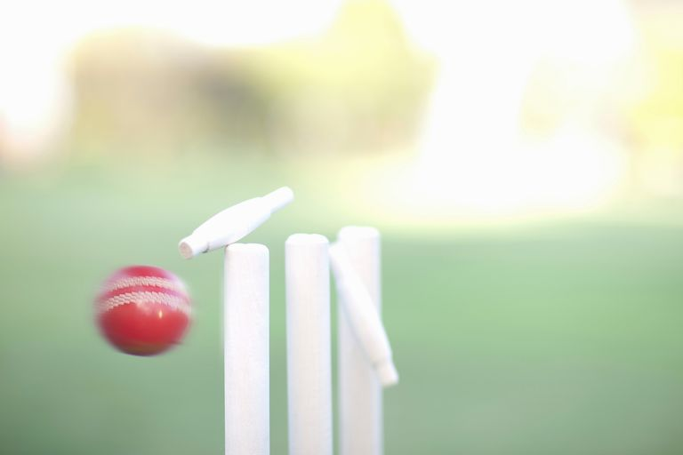 Cricket ball hitting cricket stumps, close up
