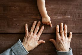 baby hand with two older hands