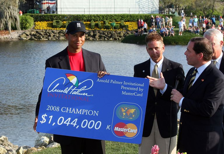 Tiger Woods gets the winner's check after an Arnold Palmer Invitational