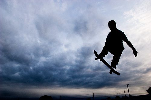 Skateboarder silhouetted against cloudy sky.