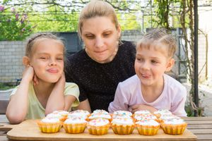 Mother and two daughters salivate looking at cupcakes