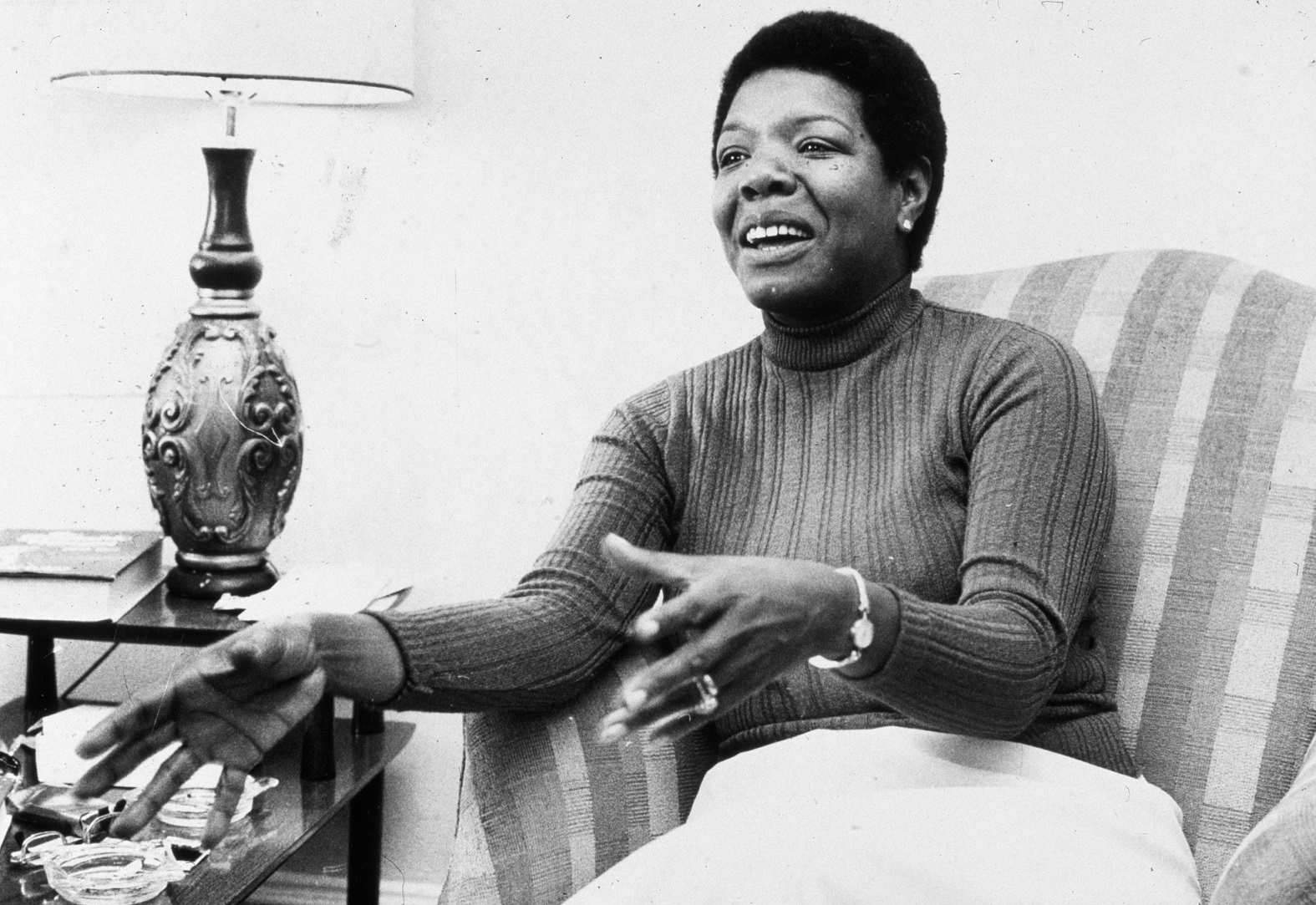 Maya Angelou sitting in a chair and talking while gesturing with hands