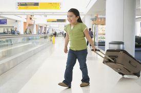 Niña con maleta en aeropuerto