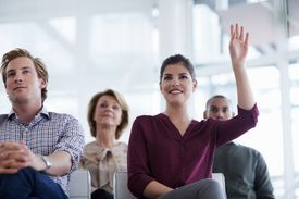 woman raising hand to ask a question.