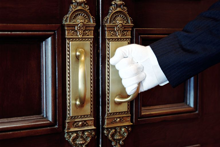 The white-gloved hand of a butler prepares to open a set of fancy doors