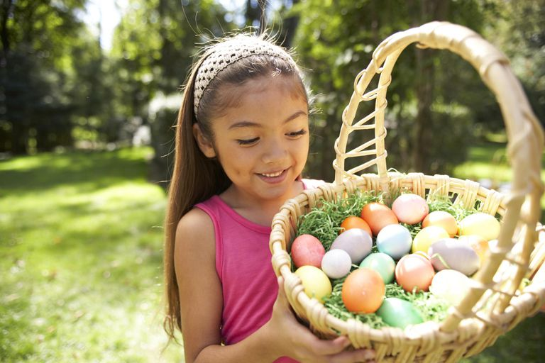Girl (6-7) holding Easter basket in garden