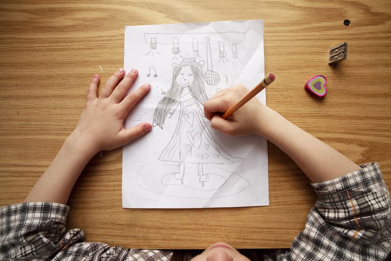 Girl drawing a person on paper