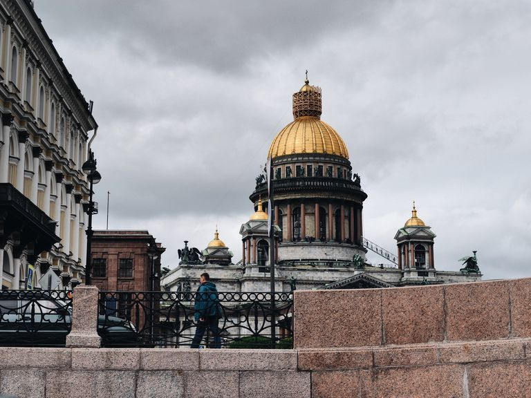 Man Walking By St Isaacs Cathedral Against Cloudy Sky