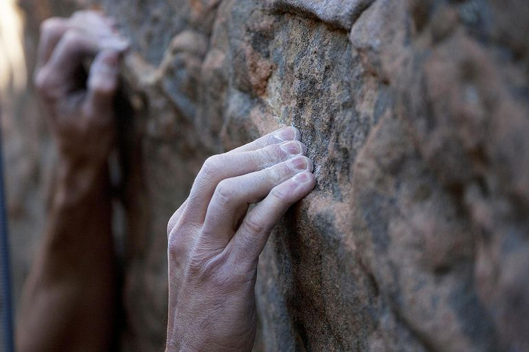 A climbers finger tips grasp a hold