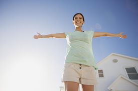 Woman smiling with arms outstretched against blue sky