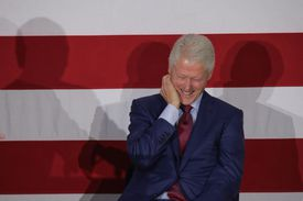Bill Clinton laughing in front of red and white stripes.