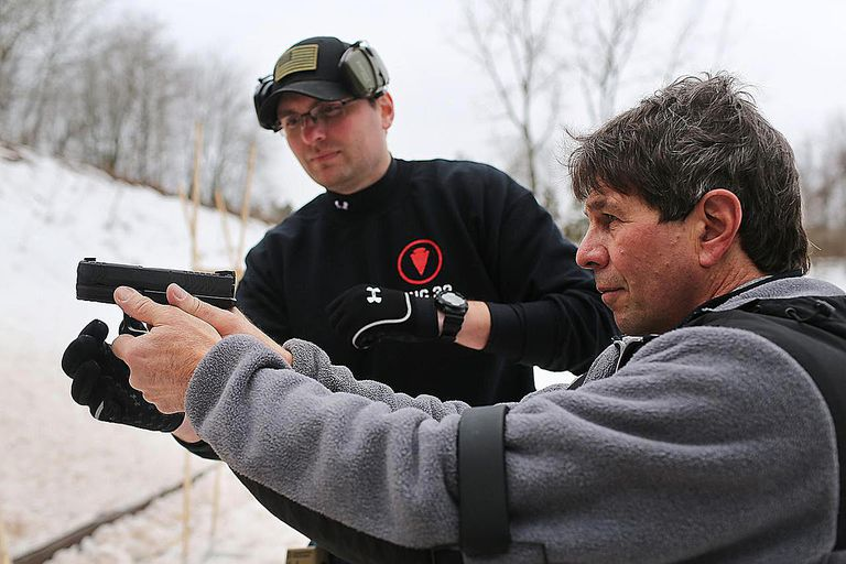 A man pointing a gun assisted by a gun safety professional