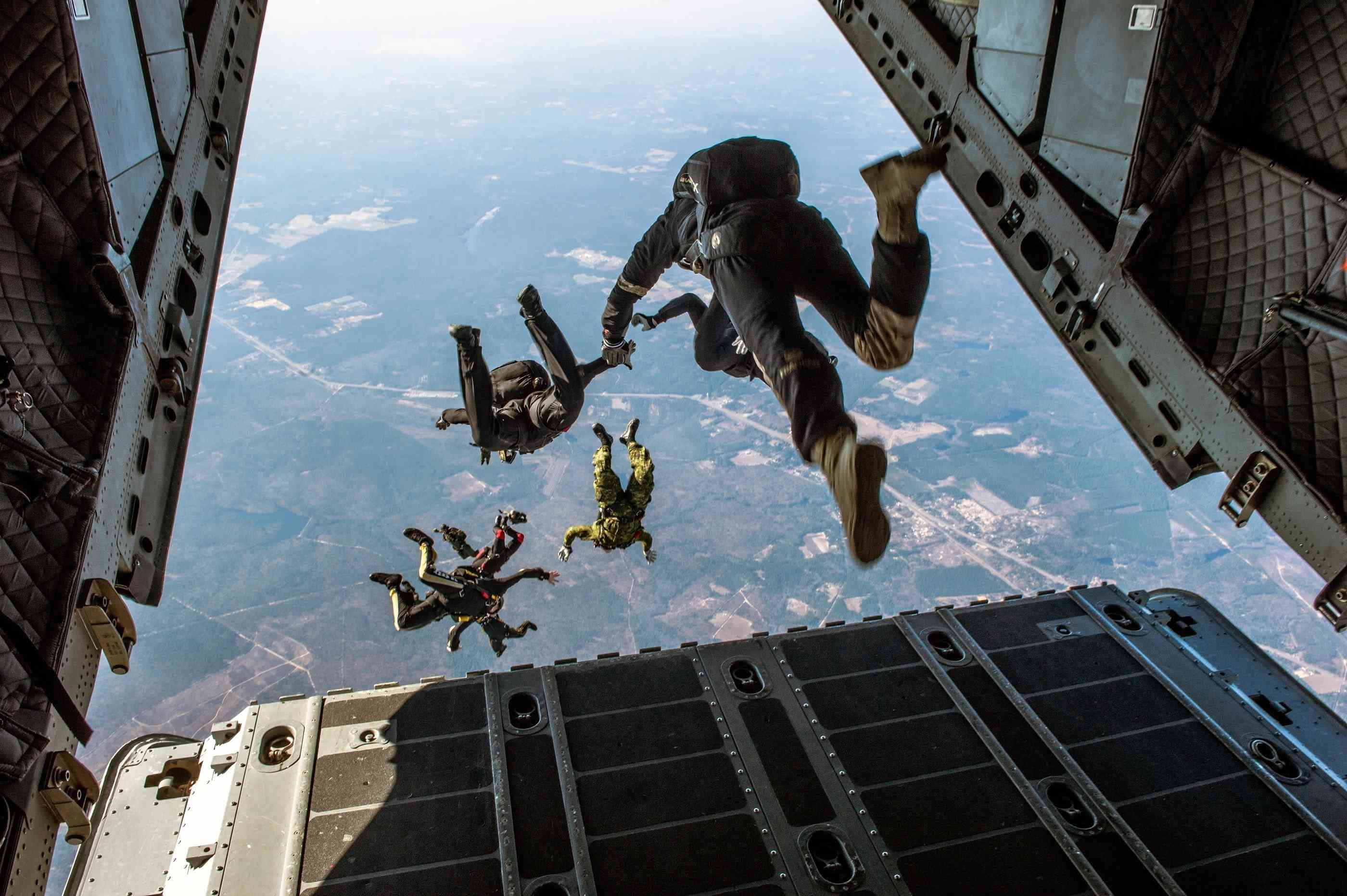 Several people jumping out of the back of a plane as seen from first person perspective.
