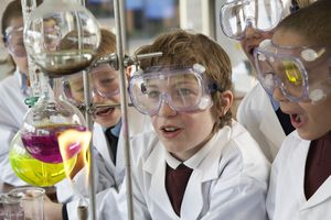 Group of children watching an experiment in a school laboratory.