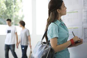 Female College Student Checking Bulletin Board