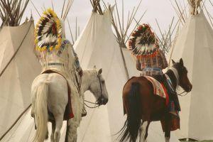 Umatilla chiefs riding horses, wearing traditional headdress, rear view