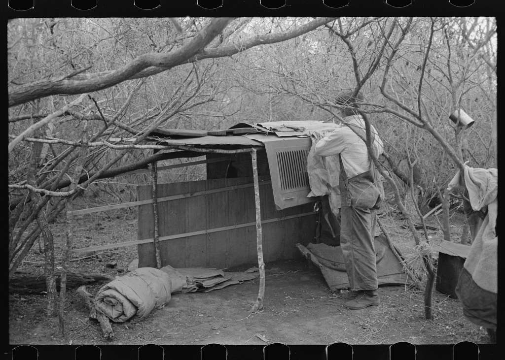 Migrant worker living in camp with two other men, working on lean-to which is to be his sleeping quarters