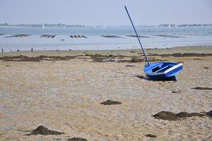 A sailboat stranded on the beach at low tide
