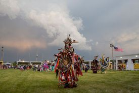 American Indians in full ceremonial dress performing a traditional dance.