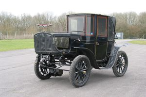 Krieger electric brougham, made in 1904, parked near an empty roadway on a sunny day.