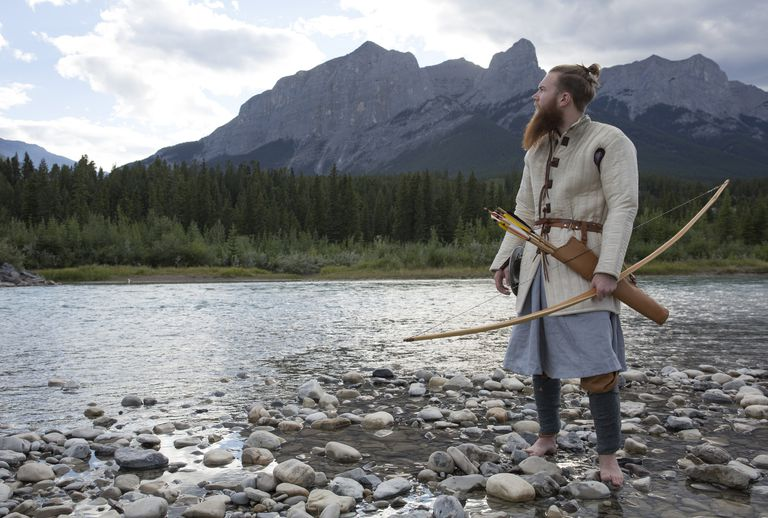 Man in viking warrior dress hunts by mtn river