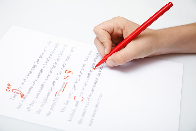 Person holding a pen editing a document