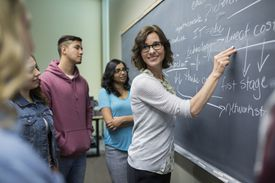 Teacher writing on chalkboard in a classroom