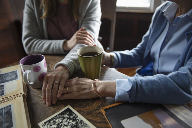 Affectionate senior mother and daughter holding hands, drinking coffee and looking at photo albums