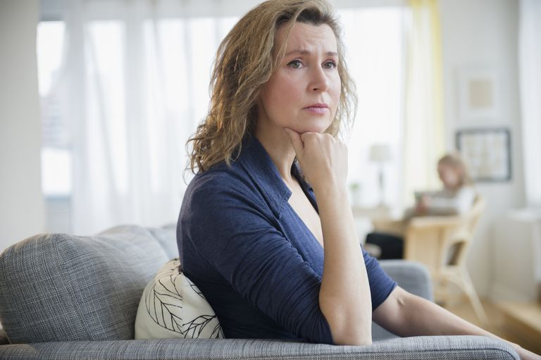 Concerned Caucasian woman sitting on sofa