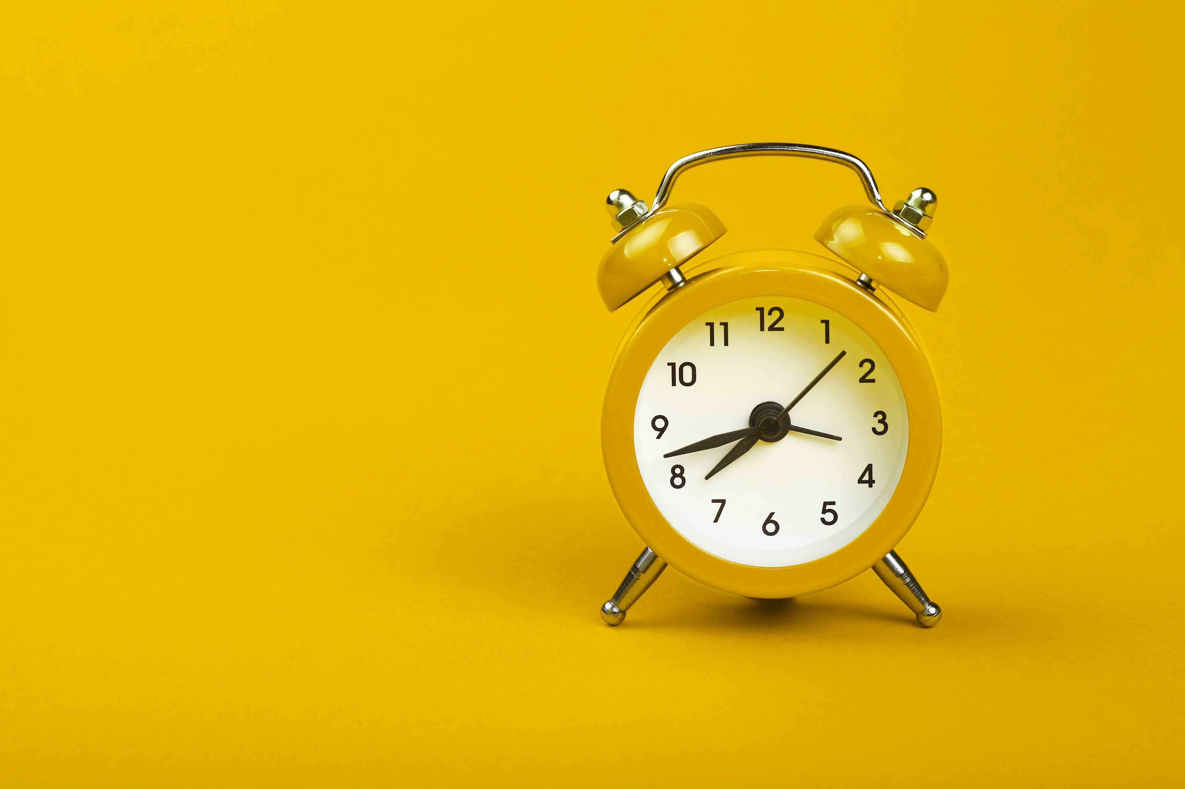 Close-Up Of Alarm Clock Over Yellow Background