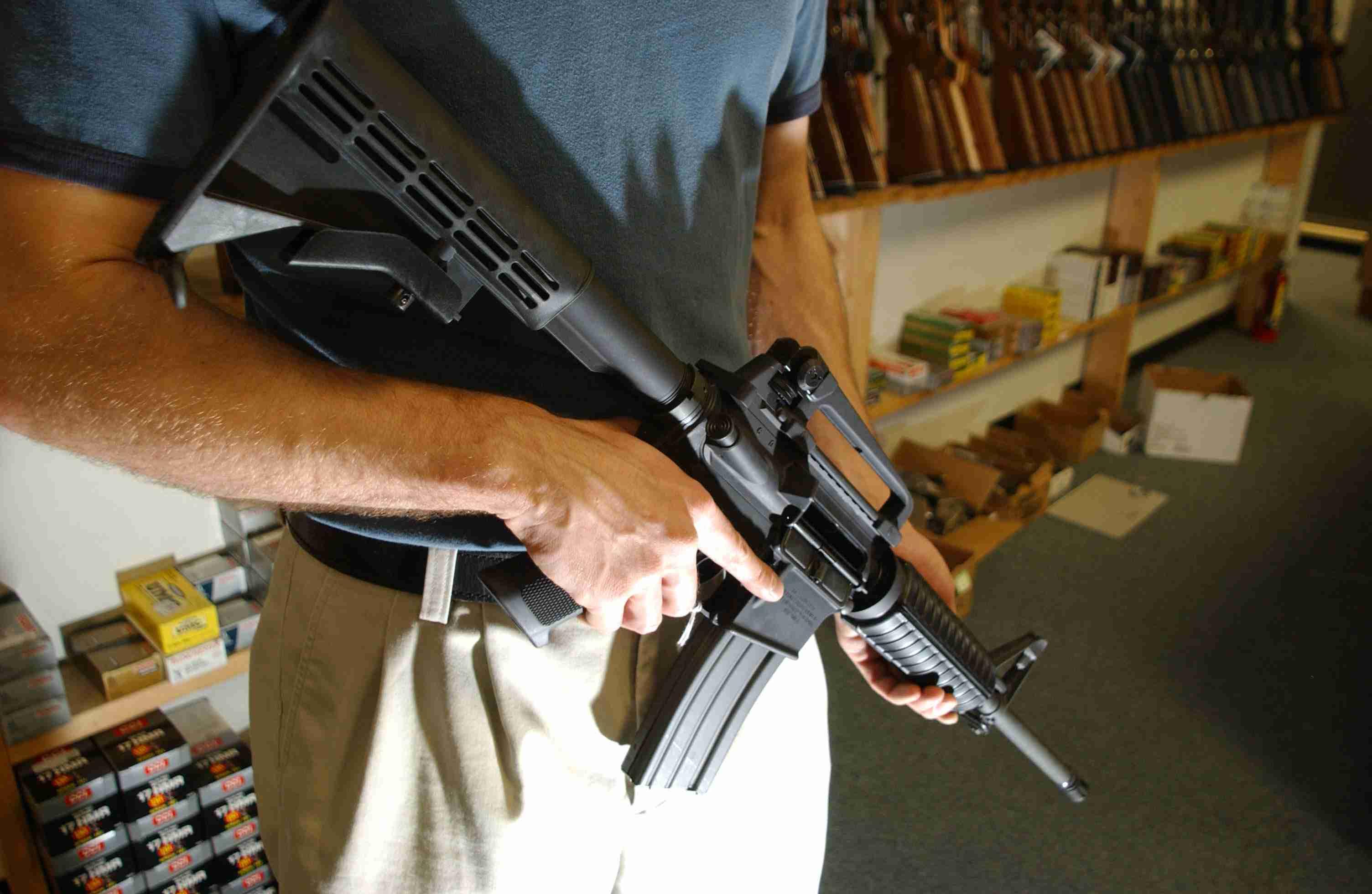 A Denver, Colo., gun dealer holds a Colt AR-15