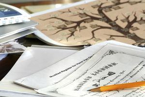 Marriage license and family tree with pencil and other documents on a table.