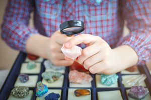 child looks at his collection of minerals