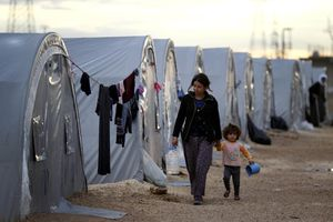 Syrian refugees from the town of Kobani walk besides their tents near Suruc on the Turkish-Syrian border, 2014 Gokhan Sahin/Getty Images