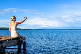 Woman sitting on a dock taking a selfie.