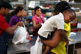 Young mother holding baby while buying groceries