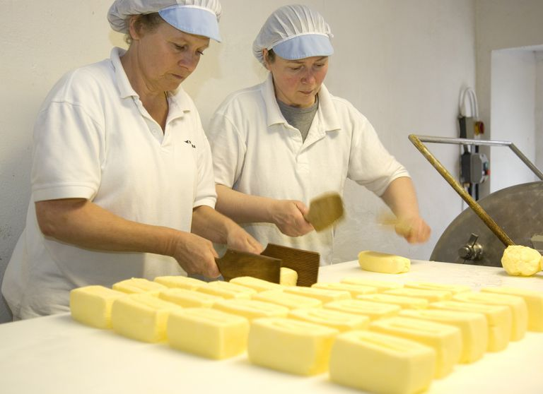 Two women making butter in dairy